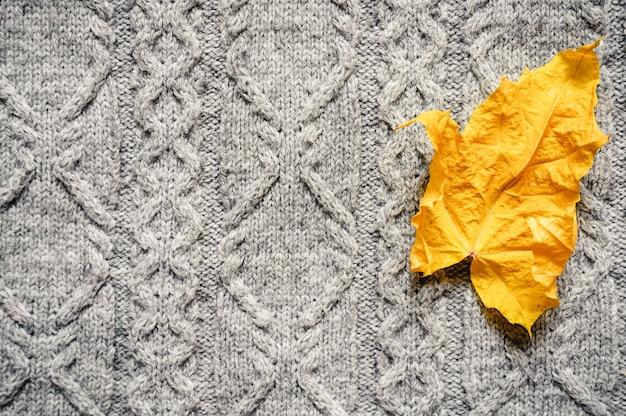 Осенний желтый сухой кленовый лист на фоне серого уютного вязаного свитера. концепция падения