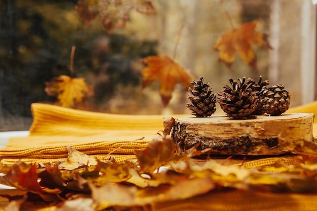 Осенний желтый лист и сосновые шишки на фоне вязанного свитера оранжевого оттенка.