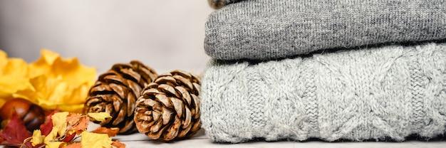 Осенние желтые кленовые листья, сосновые шишки и каштаны рядом со стопкой вязанных уютных теплых зимних свитеров нескольких оттенков серого на сером фоне. концепция падения. знамя