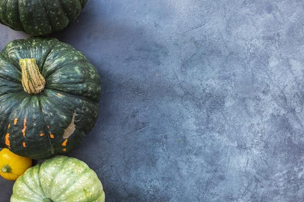 秋の背景。暗い黒い石頁岩の背景に自然な秋秋ビューカボチャ。季節の移り変わり熟した有機食品のコンセプト、ハロウィーンパーティー感謝祭。フラットレイトップビューコピースペース