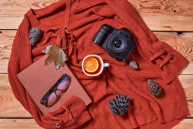 秋の背景と秋の葉の本ハーブティーとデジタル一眼レフの写真カメラ