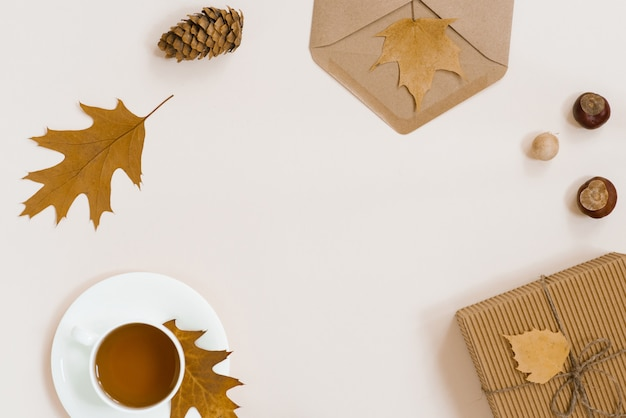 Autumnal flat lay with white knitted plaid, hot cup of tea and fallen brown leaves, crab envelope, gift box. top still life autumn  on beige light  with copyspace.