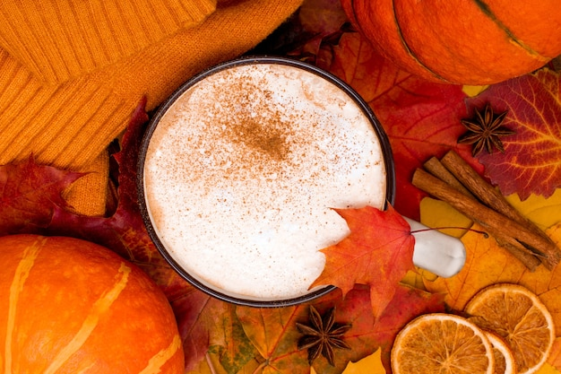 Autumnal leaves with cup of spiced coffee and cozy sweater