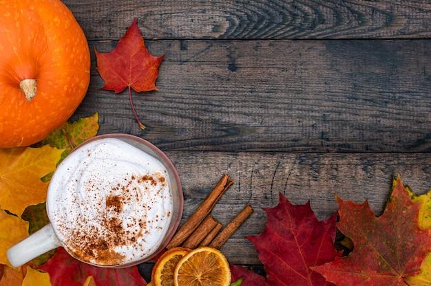 秋のカエデは、木製の背景にコーヒーとカボチャのカップとの境界線を残します。