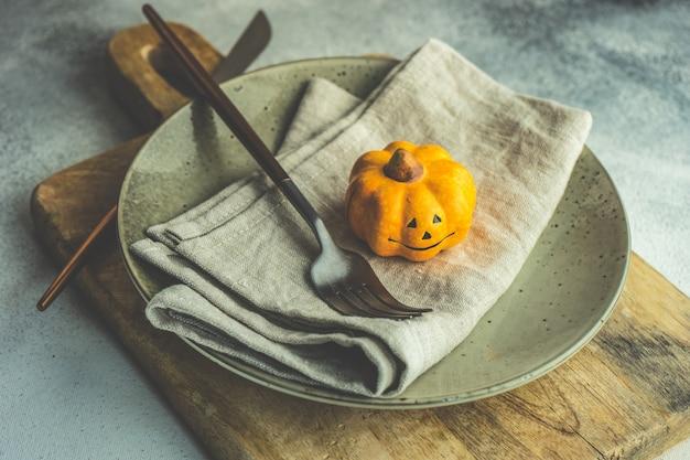 コピースペースと素朴な背景に明るいカボチャと秋のテーブルセッティング