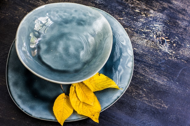 Autumnal table setting with bright yellow leaves on wooden table