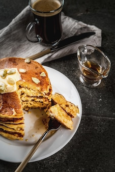 Autumnal traditional food. stack of pumpkin pancakes with butter, pumpkin seeds and maple syrup. with a cup of coffee. on a black stone table. copyspace