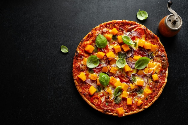Autumnal vegetarian pizza with pumpkin and vegetables on dark background.