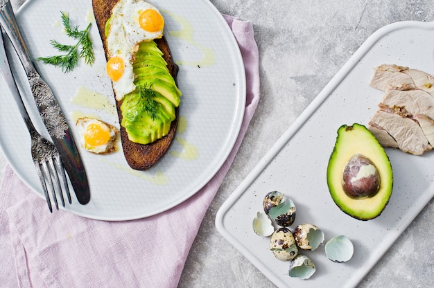 Avacado sandwich with egg on toast of black bread.