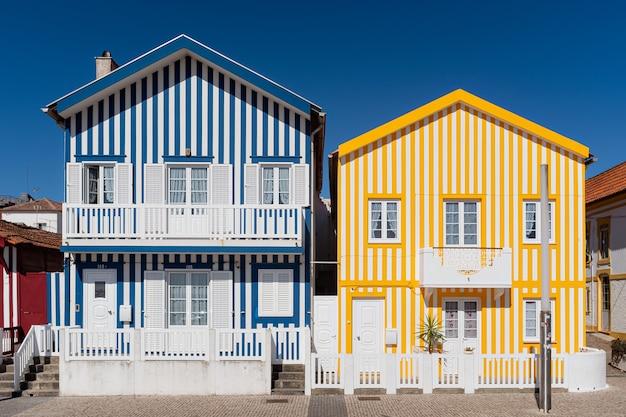 Авейру, португалия, типичные рыбацкие дома в полосатых тонах на побережье коста-нова