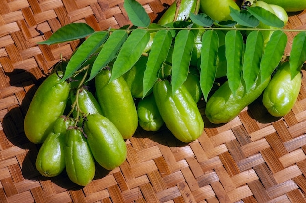Averrhoa bilimbi and green leaves on woven bamboos, known as bilimbi fruit, cucumber tree, a fruit-bearing tree of the genus averrhoa, many benefits and vitamins for health, selected focus.