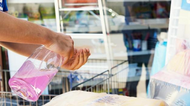 Аветрана, италия, - март, 13, 2020 год. аветрана, италия, - март, 13, 2020 год. перед тем, как войти в магазин, человек моет руки спиртовым дезинфицирующим средством. дезинфицирующее средство для рук вне магазина