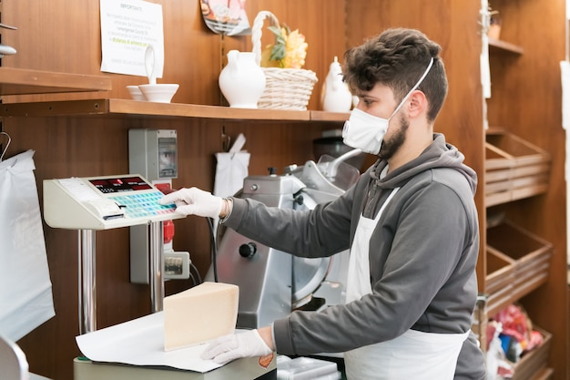 Avetrana, italy, - marth 19, 2020. salesman is serving a costumer a cheese, wearing medical mask and gloves protection during coronavirus epidemy. shopping, pandemia of covid-19