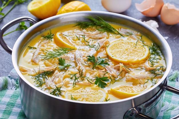 アヴゴレモノ-背景に材料が入ったコンクリートのテーブルのキャセロールにレモンとハーブが入ったおいしいクリーミーなギリシャ風チキンスープ、上からの眺め、クローズアップ