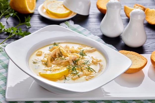 Avgolemono - delicious creamy greek chicken soup with lemon, egg yolk, pasta risini and herbs in a white bowl on a black wooden table with napkin, side view from above, close-up