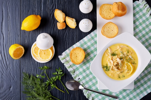 Avgolemono - delicious creamy greek chicken soup with lemon, egg yolk, pasta risini and herbs in a white bowl on a black wooden table with napkin and spoon, classic recipe, close-up