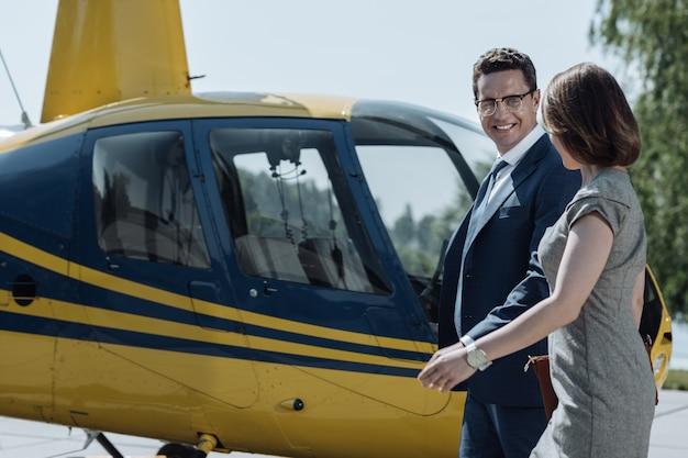 Заядлые путешественники. жизнерадостные деловые партнеры болтают и обмениваются улыбками, приближаясь к вертолету, готовому к полету