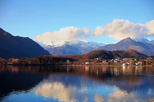 잔잔한 호수에 하늘과 산이 반사된 아빌리아나 마을 풍경
