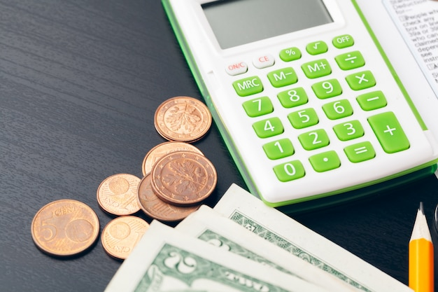 Avings, finances, economy and home concept - close up of calculator counting money and making notes at home