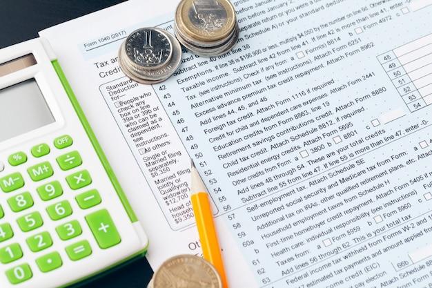 Avings、財政、経済および家のコンセプト-お金を数えると自宅でメモを作る電卓のクローズアップ