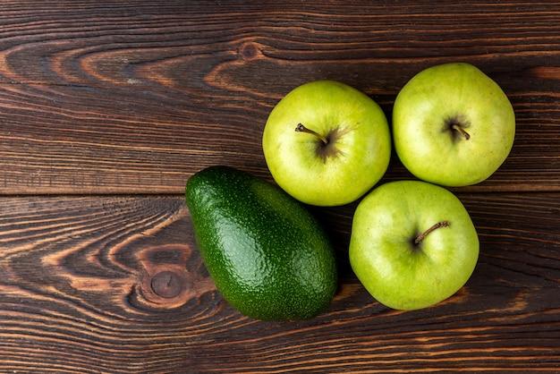 Авокадо и зеленое яблоко на столе