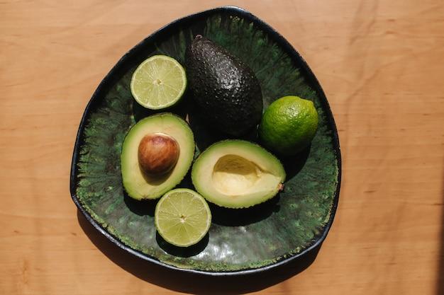 Половинки авокадо и лайма на зеленой тарелке. концепция вегетарианской пищи. вид сверху