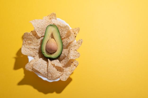 Плоское блюдо из авокадо и начо в виде концепции гуакамоле на простом ярком столе