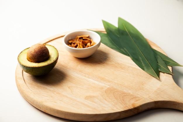 木の板にアボカドとナッツ。たんぱく質が豊富な健康食品。テーブルの上の健康的な脂肪でいっぱいの成分。高品質の写真。
