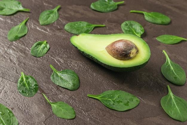 아보카도와 시금치는 돌 배경에 나뭇잎. 음료와 샐러드 재료입니다.