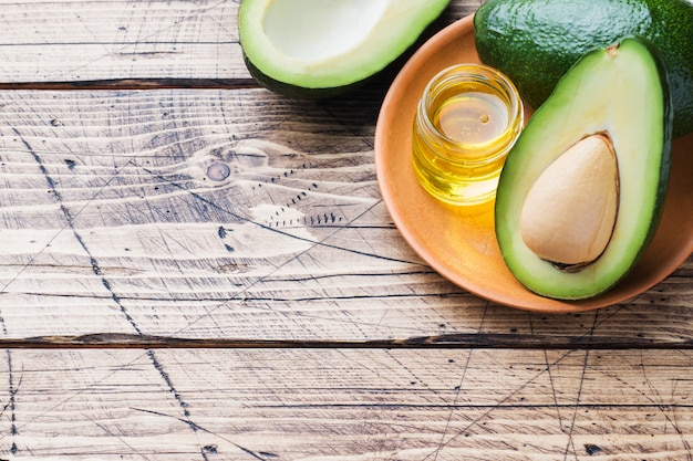 Avocado and avocado oil on wood background with copy space.