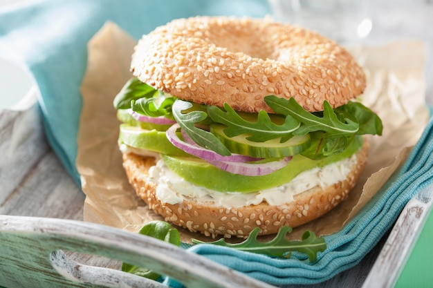 Avocado bagel with cream cheese, onion, cucumber and arugula