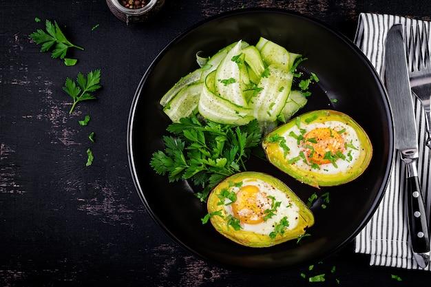 Авокадо, запеченный с яйцом и свежим салатом. вегетарианское блюдо. вид сверху, накладные расходы. кетогенная диета. кето еда