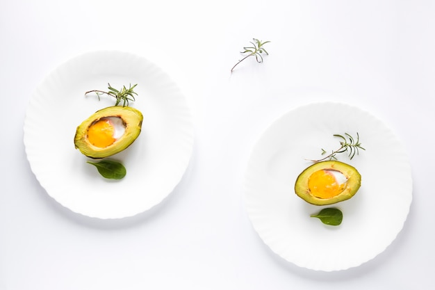 Avocado baked with egg in a plate over white background