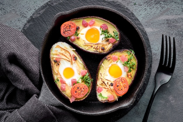Avocado boats with ham cubes, quail eggs, cheese and cherry tomatoes on iron cast skillet