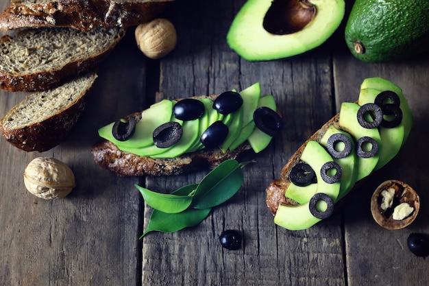 Оливки хлеба авокадо на деревянных фоне