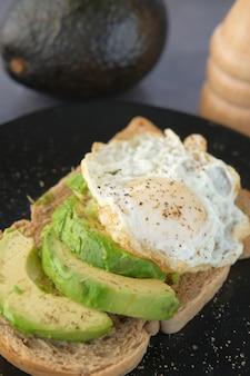 Яйцо коричневого хлеба авокадо и розмарин на столе