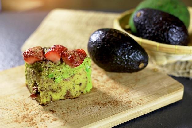 Avocado cake, strawberry on top almond powder cranberry blueberry inside.