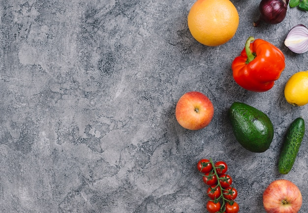 Avocado; capsicum; orange; apple; cucumber; lemon and cherry tomatoes on concrete textured backdrop