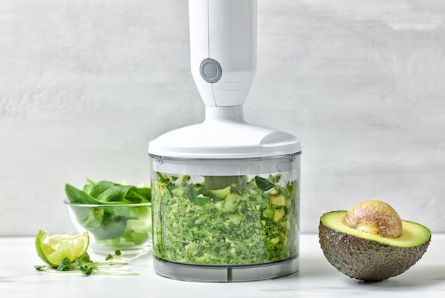 식탁에서 건강한 아침 식사 스무디를 만들기 위한 플라스틱 투명 블렌더 용기에 아보카도, 셀러리, 시금치