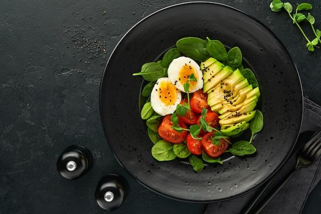 아보카도, 체리 토마토, 시금치, 닭고기 달걀, 마이크로그린 완두콩, 검은 참깨 신선한 샐러드를 검은색 슬레이트, 돌 또는 콘크리트 배경에 있는 검은 그릇에 담습니다. 건강 식품 개념입니다. 평면도.