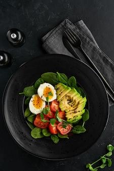 アボカド、チェリートマト、ほうれん草と鶏卵、マイクログリーンピース、黒ゴマの新鮮なサラダを黒のスレート、石、またはコンクリートの背景に黒のボウルに入れます。健康食品のコンセプト。上面図。
