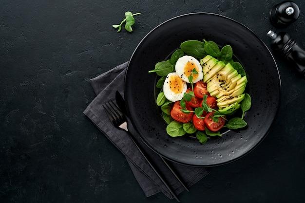 아보카도, 체리 토마토, 시금치 및 닭고기 달걀, 마이크로 그린 완두콩 및 검은 참깨 검은 슬레이트, 돌 또는 콘크리트 배경에 검은 그릇에 신선한 샐러드. 건강 식품 개념. 평면도.