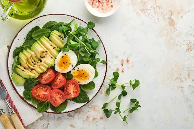 아보카도, 체리 토마토, 시금치, 닭고기 달걀, 마이크로그린 완두콩, 검은 참깨 신선한 샐러드가 하얀 돌 탁자 배경에 있는 그릇에 담겨 있습니다. 건강한 아침 식사 음식 개념입니다. 평면도.