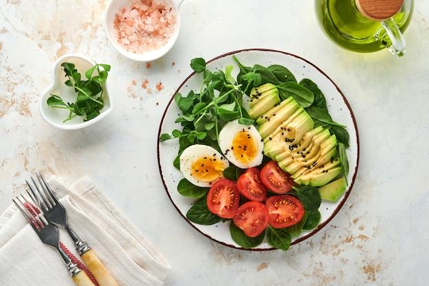 アボカド、チェリートマト、ほうれん草、鶏卵、マイクログリーンピース、黒ゴマの新鮮なサラダを白い石のテーブルの背景にボウルに入れます。健康的な朝食食品のコンセプト。上面図。