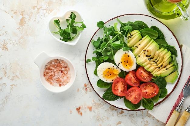 아보카도, 체리 토마토, 시금치 및 닭고기 달걀, microgreens 완두콩 및 검은 참깨 흰 돌 테이블 배경에 그릇에 신선한 샐러드. 건강한 아침 식사 음식 개념입니다. 평면도.