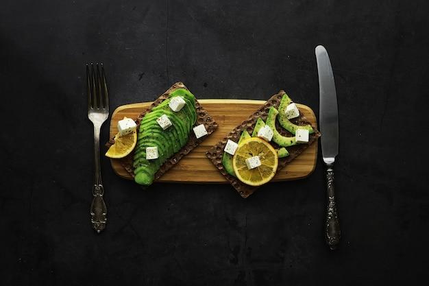 アボカド料理のレシピ。木製のまな板に熟した緑色のアボカドを添えて。