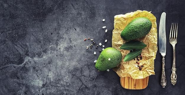아보카도 요리법. 봉사를 위한 나무 커팅 보드에 익은 녹색 아보카도.