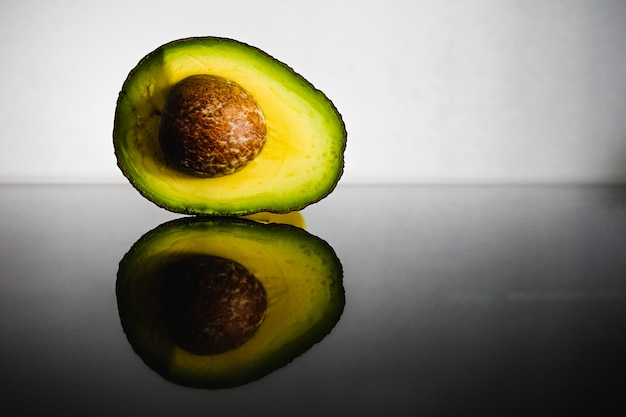 Avocado, cross section, with its reflection in a black surface of a kitchen.