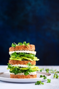 아보카도, 오이, 페타 치즈 샌드위치는 건강한 아침 식사를 위한 간단한 나무 스탠드에 마이크로 그린과 잡곡 빵으로 장식되어 있습니다. 선택적 초점