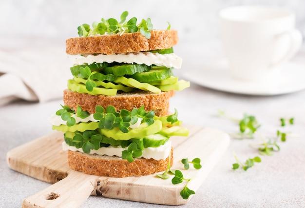 아보카도, 오이, 페타 치즈 샌드위치는 마이크로 그린과 잡곡 빵으로 장식 된 간단한 나무 스탠드에 건강한 아침 식사를 제공합니다. 선택적 초점.